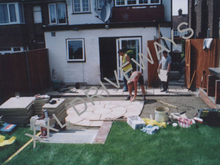 Process of a patio rear garden with patio steps leading to grass area.